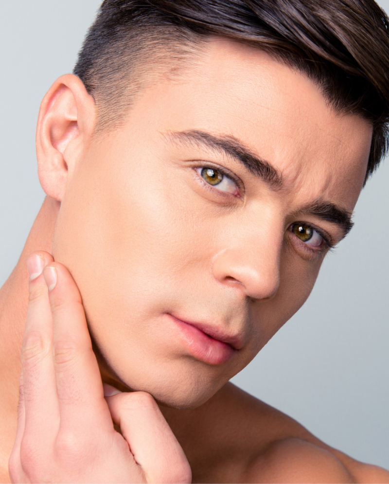 Man with acne scarring touching his face