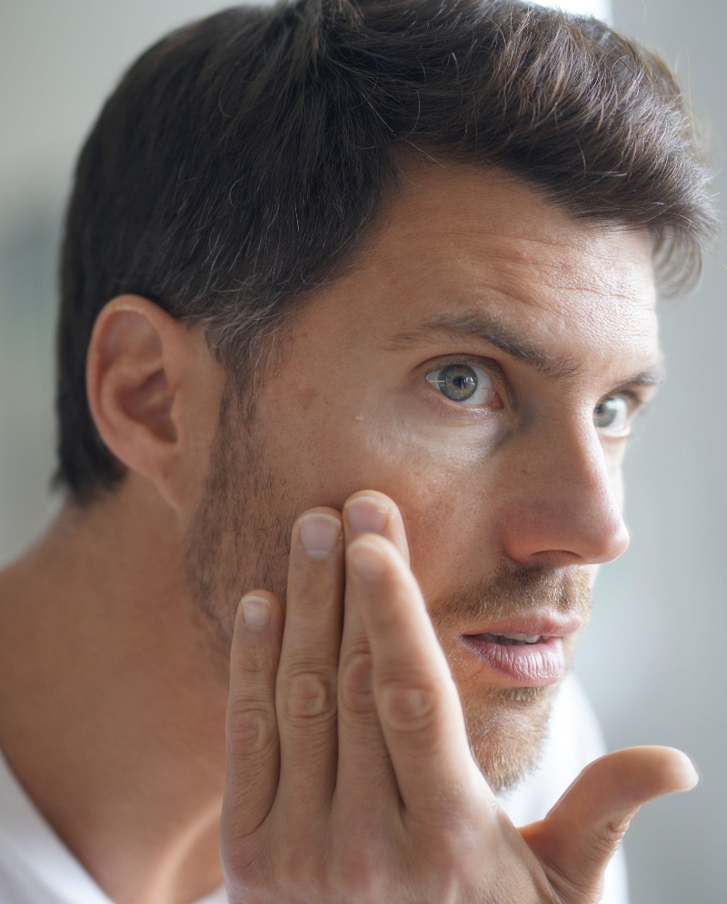 Man with age spots on his face checking out his skin in the mirror