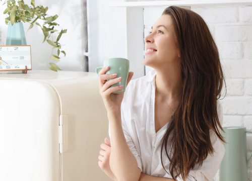 Happy woman holding a coffee cup in her living room