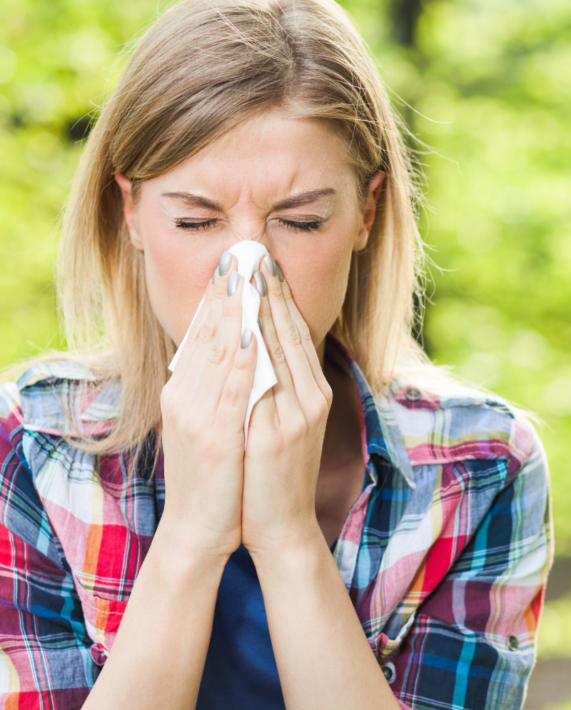 Blonde woman blowing her nose into a tissue