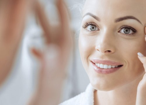 Woman looking at her face in the mirror after AquaGold® fine touch™ treatments