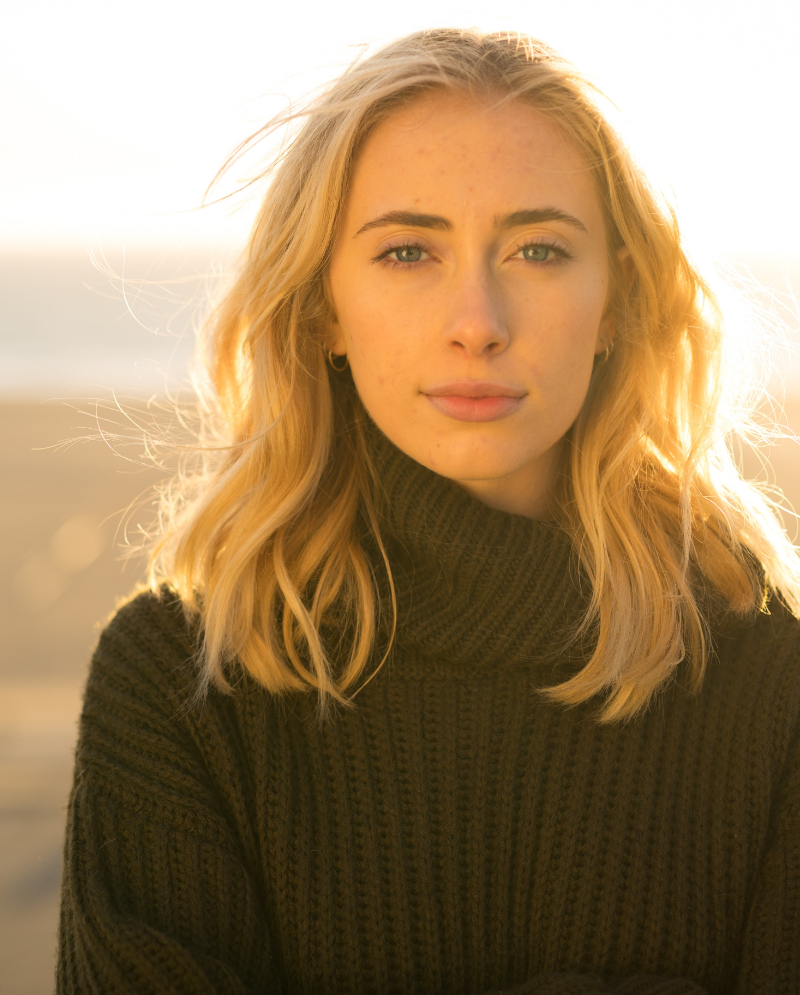 Blonde woman with Autoimmune Diseases wearing a sweater outside in the sunlight