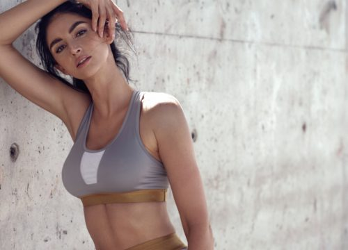 Woman in exercise clothes leaning against a concrete wall