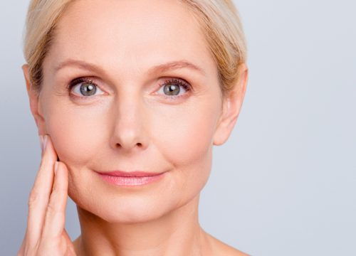Older woman with facial volume loss touching her face