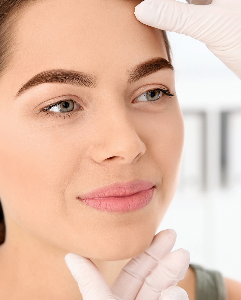 Dermatologist looking at female patient's face