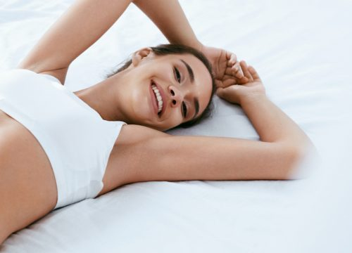 Woman in her underwear smiling and lying down in bed