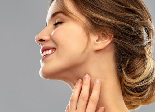 Woman touching her submental area after KYBELLA® chin treatments