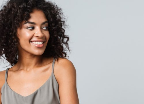 Smiling woman wearing a gray dress with slight keloids on her skin