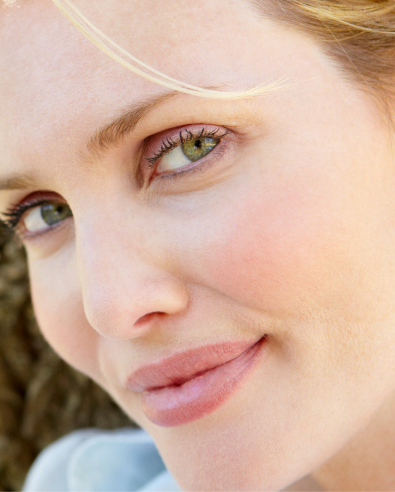 Close-up on a blonde woman's green eyes