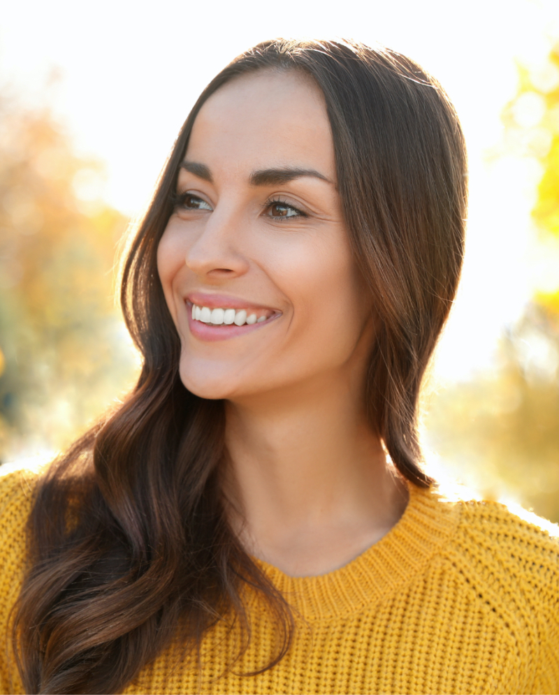 Smiling woman wearing a yellow sweater outdoors
