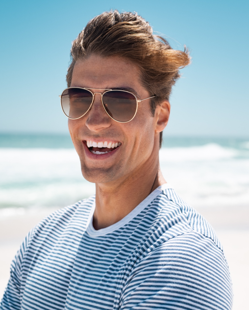 Man wearing sunglasses smiling at the beach