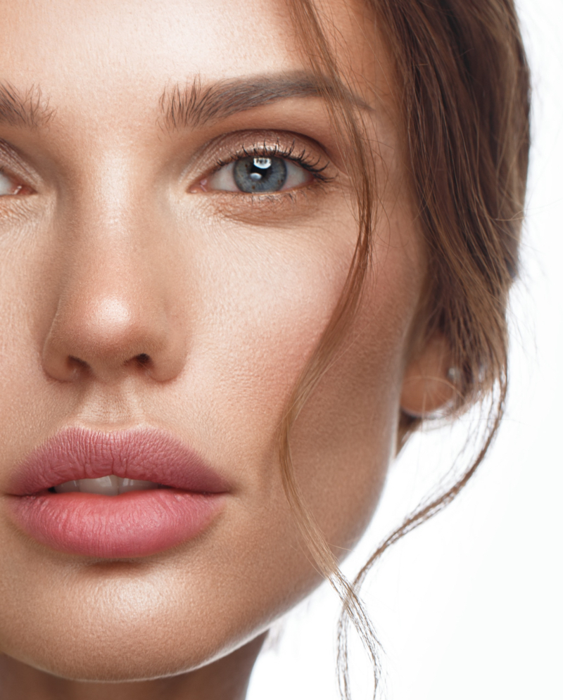 Close=up on a woman's face, green eyes, and full lips