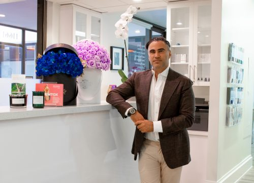 Dr. Kia standing by the front desk reception area